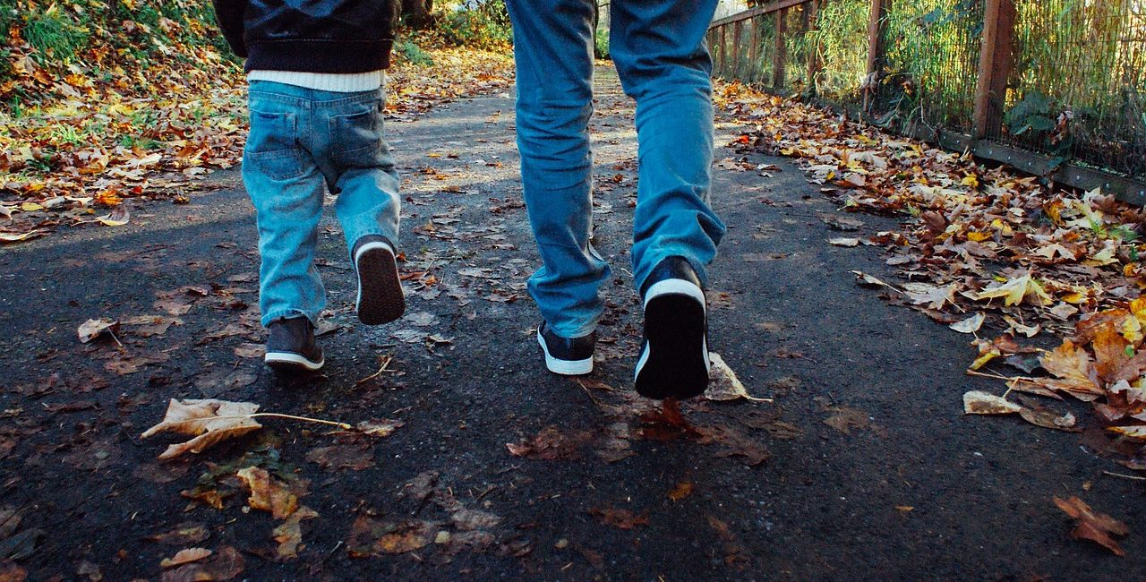 Adult and child's legs in jeans walking along a leafy path