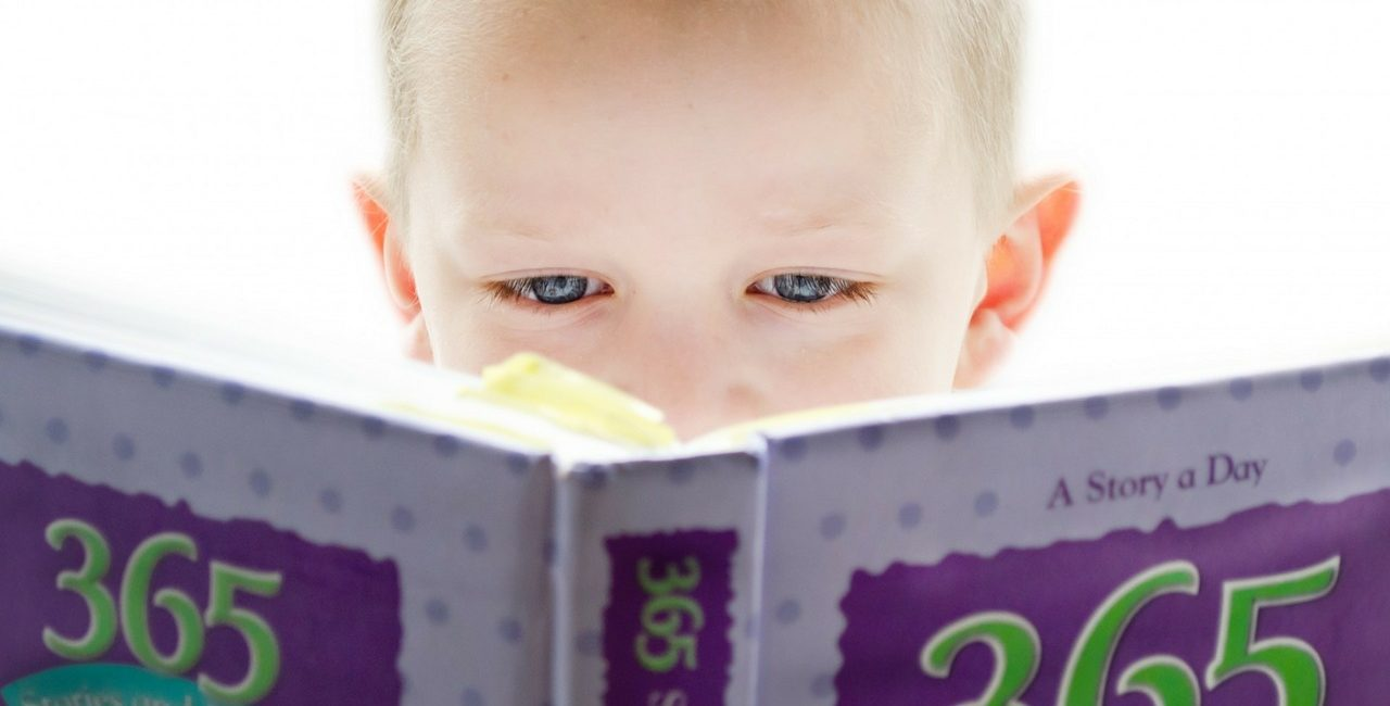 Small child holding and looking at a book