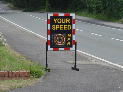 Speed indicator device on pavement with red and white frame and words your speed with a smily face