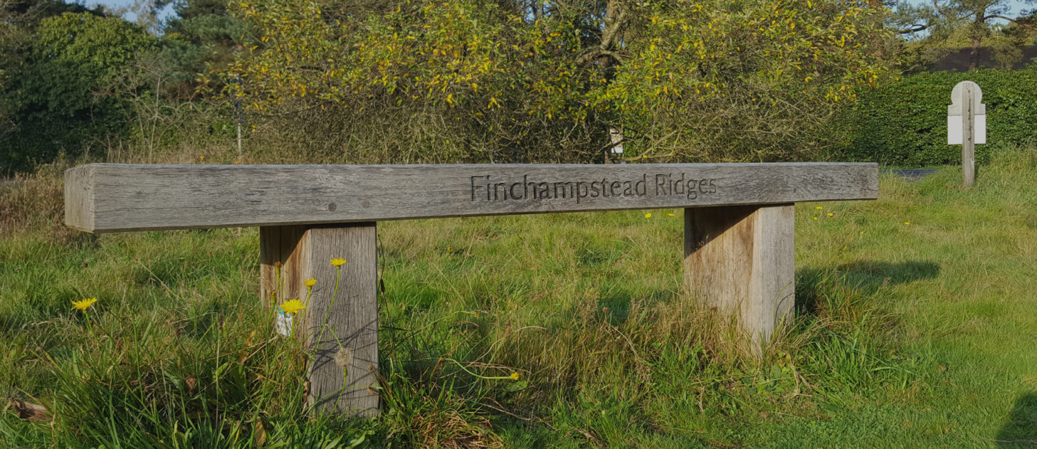 Wooden bench in grass with Finchampstead Ridges engraved on it