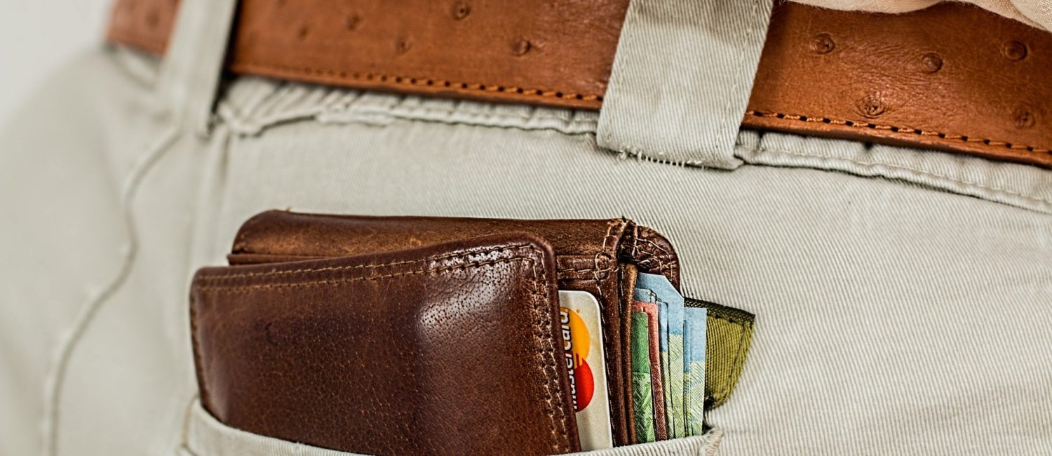 Bulging leather wallet with cards and notes sticking out of a back pocket