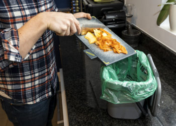 Person scraping food waste in to a caddy