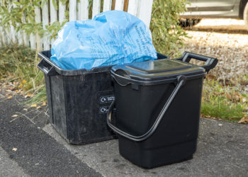 Black recycling box with blue recyling bag in it next to a black food waste caddy