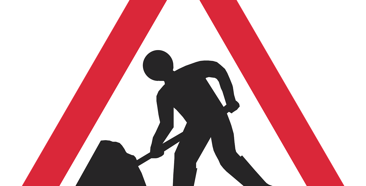 Triangular warning road sign with red edge showing man digging