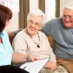 Friendly person speaking to smiling elderly man and woman