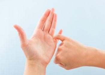 ingerspelling alphabet. Female hands isolated on blue background showing deaf mute BSL alphabet letter S.