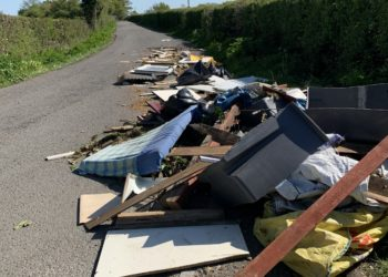 Heap of flytipping by a road including mattress and planks