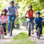 Man, woman, girl and boy cycling wearing helmets and smiling
