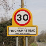 Yellow welcome to Finchampstead gateway sign with 30 mph roundel