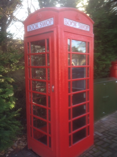 Traditional red telephone box with book swop signs