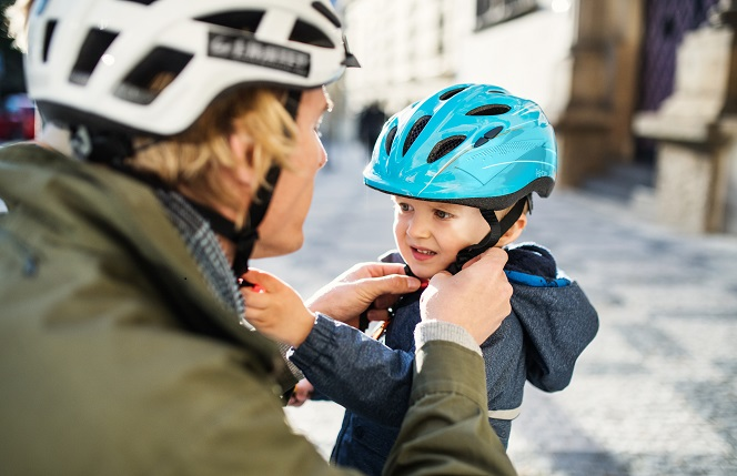 parent wearing cycle helmet putting a helmet on a child