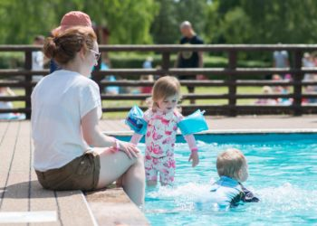 young children in paddling pool with lady sitting with feet in pool