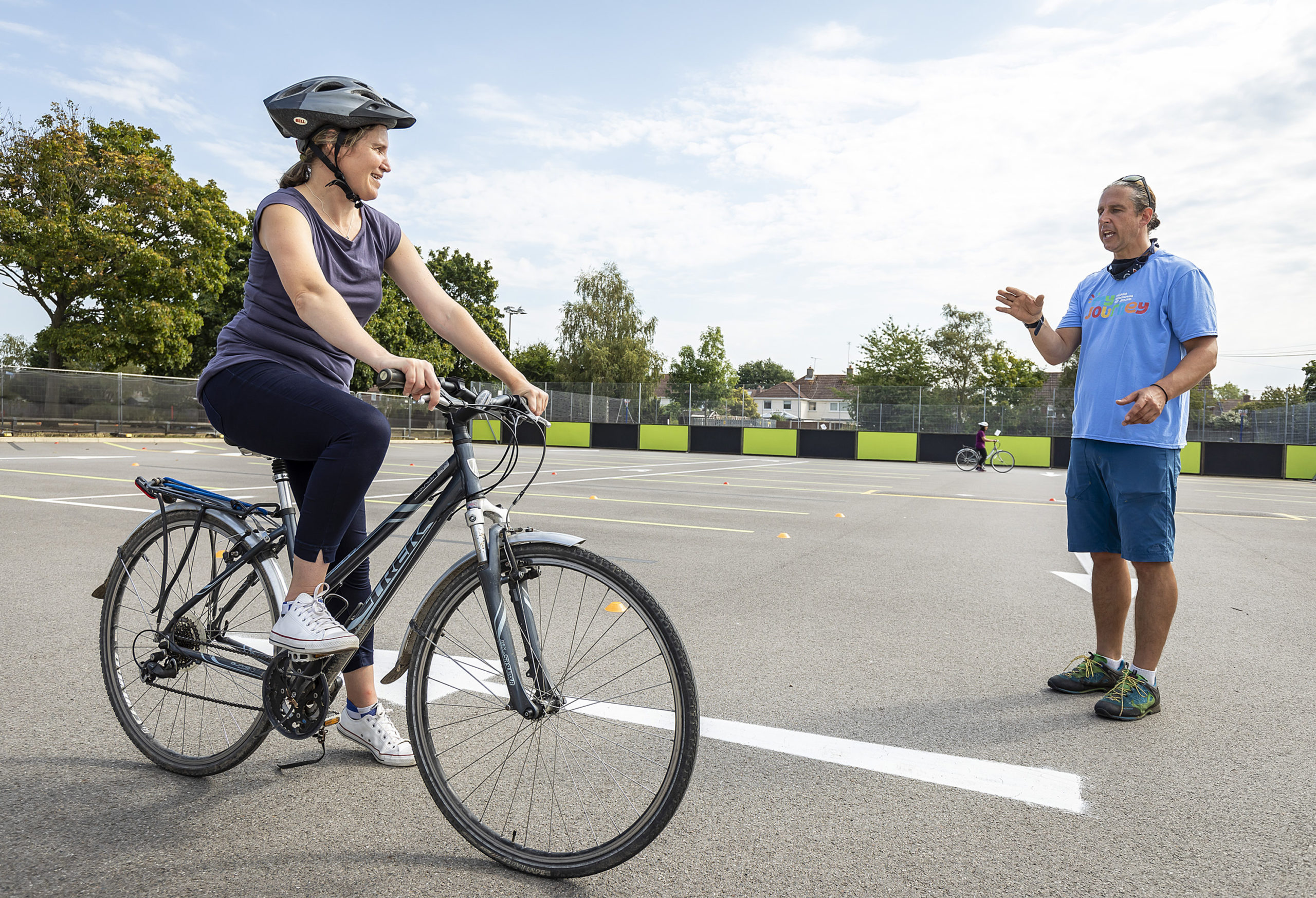 Lady on bicycle with man giving instructions
