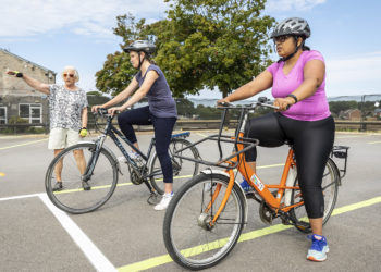 Two ladies on bicycles with lady giving instructions