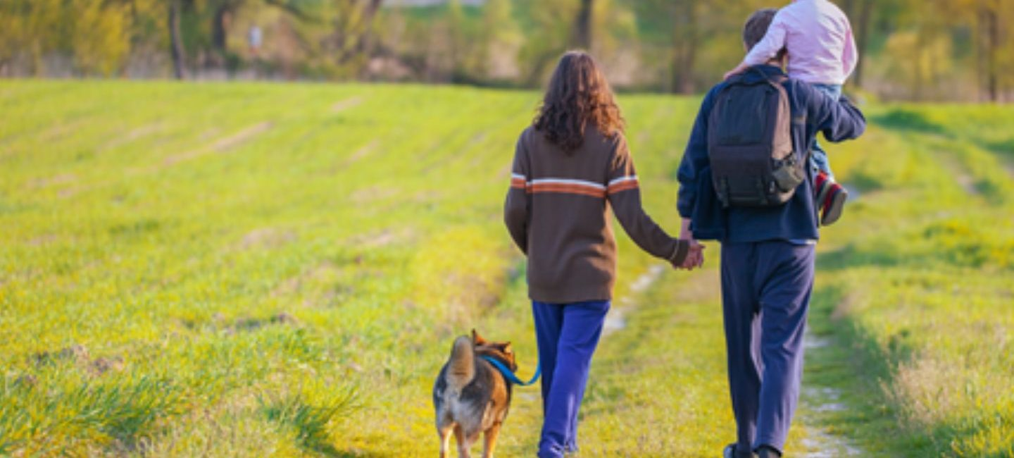 man and woman with dog and small child walking through countryside
