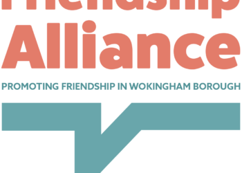 Friendship Alliance logo with red writing on a grey and white checked background