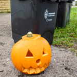 Carved pumpkin beside black food waste bins