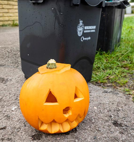 Carved pumpkin beside black food waste bins