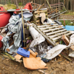 Pile of flytipped wasted including orange sofa and pallets and metal gate