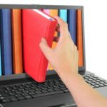 Laptop with hand taking a red book out of the screen
