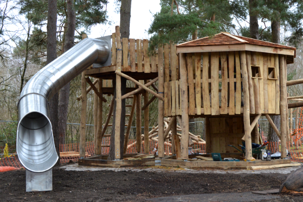 Wooden play house with long tubular metal slide and ladders