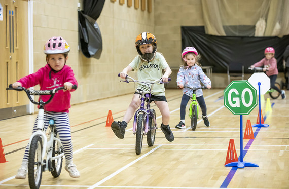 Young children on balance bikes in a sports hall