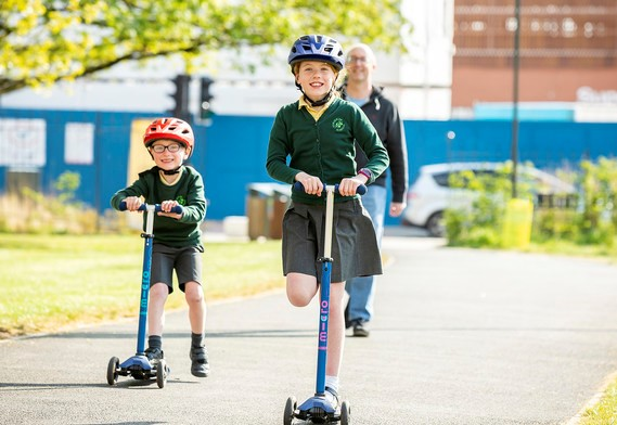 Young boy and girl in school uniform on scooters wearing cycle helmets