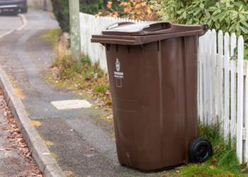 Brown wheelie bin on pavement beside a white picket fence