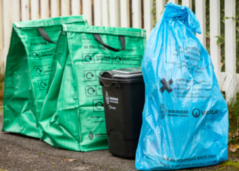 Two green recycling bags next to a black food waste caddy and a blue waste bag